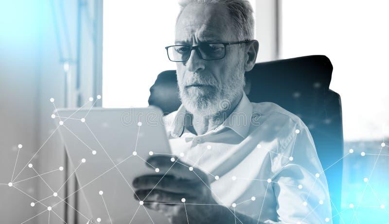 Hög affärsman som använder en digital minnestavla; ljus effekt royaltyfri bild