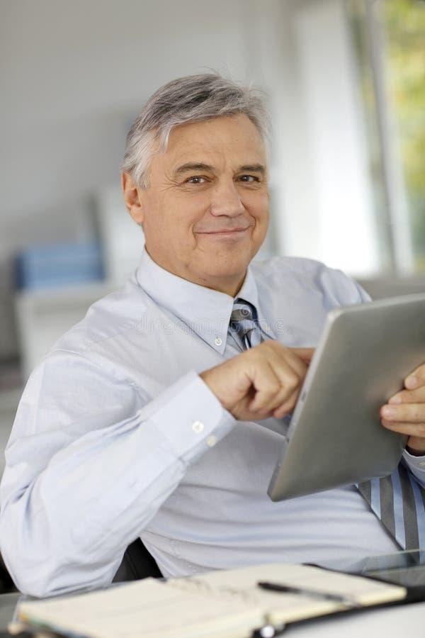 Hög affärsman som använder minnestavlan royaltyfri bild
