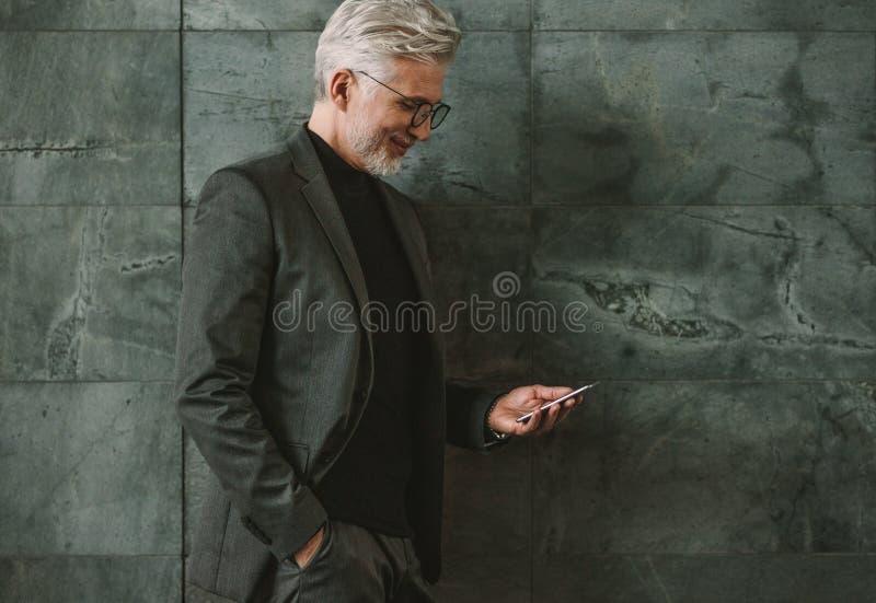 Hög affärsman som använder mobiltelefonen royaltyfri foto
