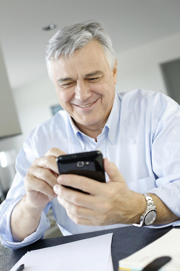 Hög affärsman som använder smartphonen royaltyfri fotografi