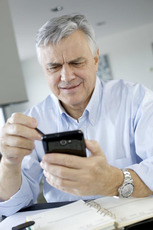 Hög affärsman som använder smartphonen royaltyfri foto