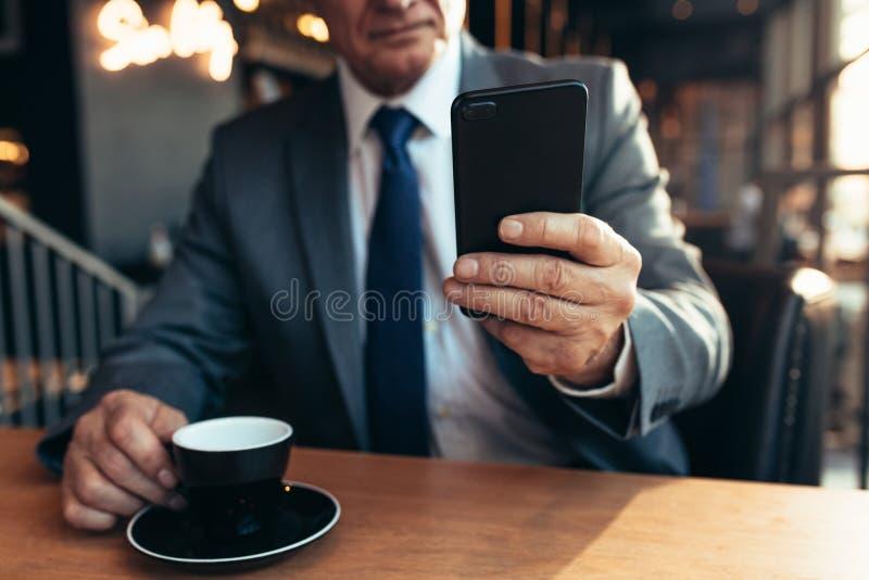 Hög affärsman som använder smartphonen på coffee shop arkivbilder