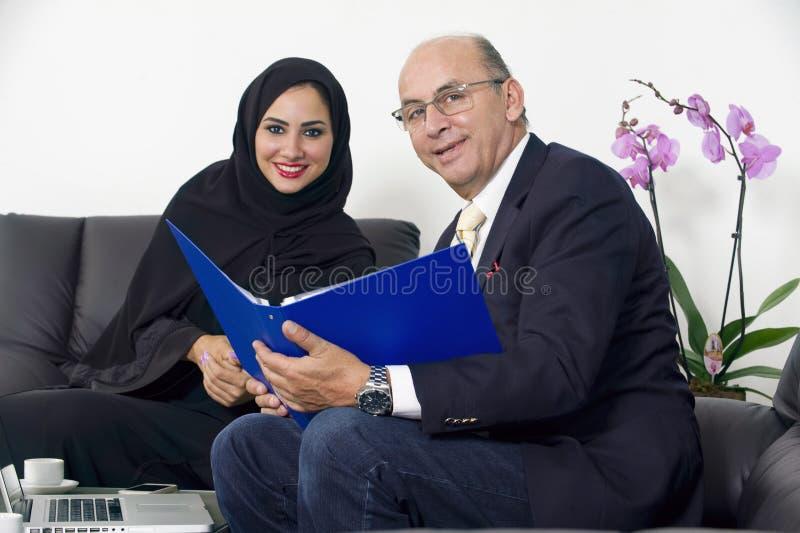 Hög affärsman som arbetar med bärande hijab för arabisk affärskvinna arkivfoton