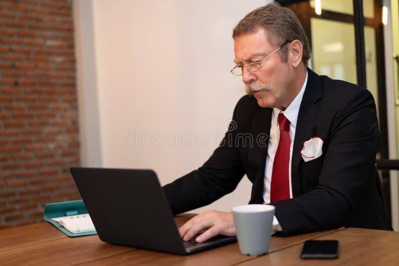 Hög affärsman som arbetar med bärbara datorn i vindkontoret fotografering för bildbyråer
