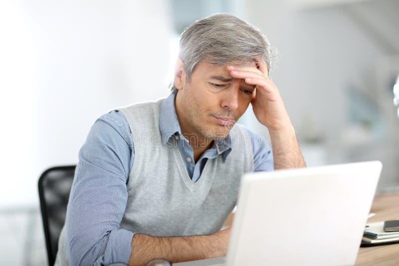 Hög affärsman som arbetar på bärbara datorn som lider en huvudvärk fotografering för bildbyråer