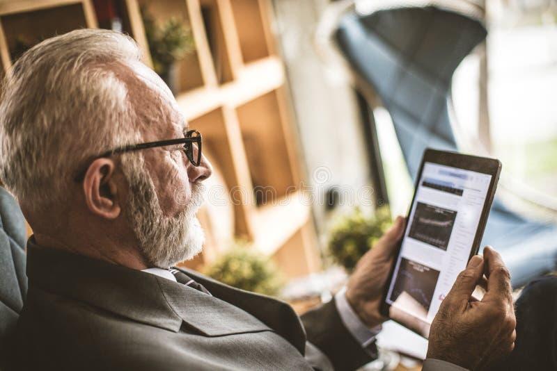Hög affärsman som arbetar på hans digitala minnestavla close upp arkivfoton