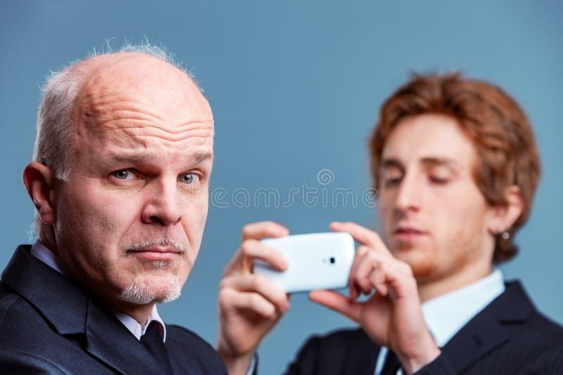 Hög affärsman som drar en retsam framsida royaltyfri foto