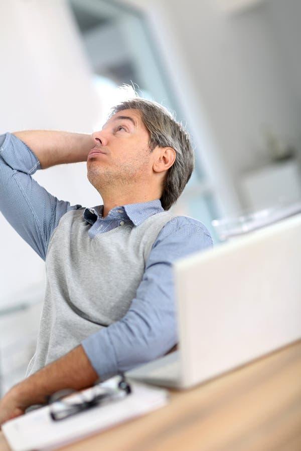 Hög affärsman som får tröttad av att arbeta royaltyfri fotografi