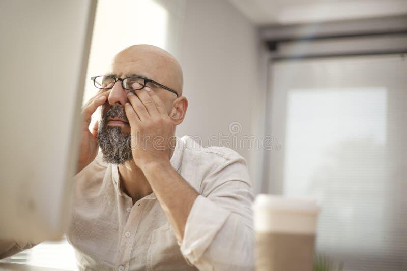 Hög affärsman som gnider hans trötta ögon royaltyfri bild