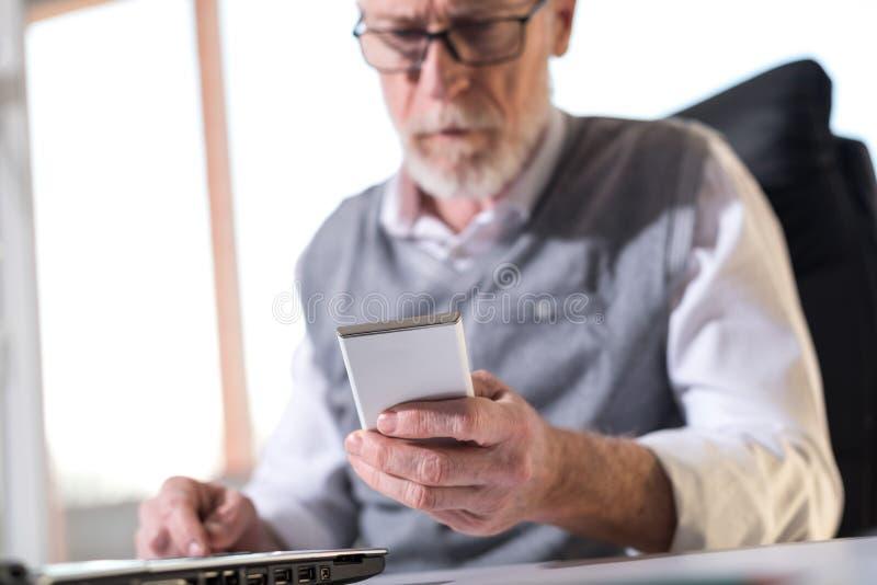 Hög affärsman som läser ett meddelande på hans mobiltelefon, hårt ljus royaltyfri bild