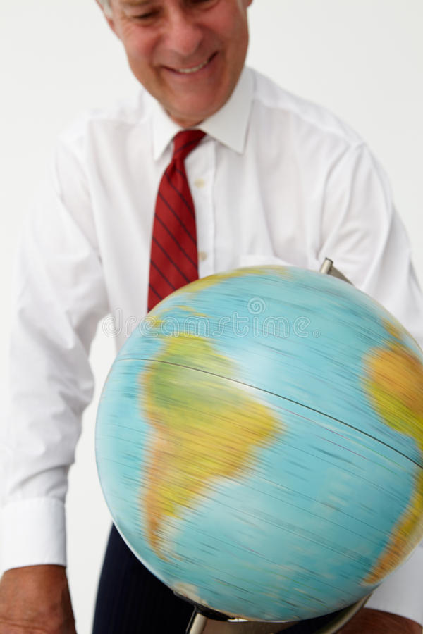 Hög affärsman som ser och rotera ett jordklot royaltyfria bilder