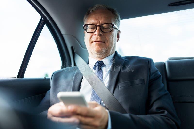 Hög affärsman som smsar på smartphonen i bil arkivfoton