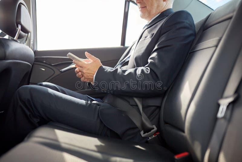 Hög affärsman som smsar på smartphonen i bil arkivfoto