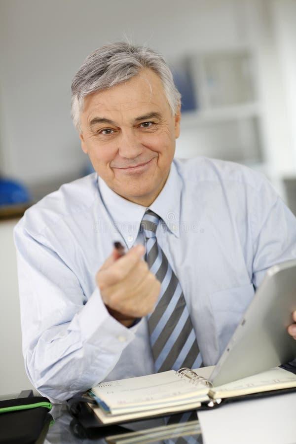 Hög affärsman som talar till klienten arkivfoton