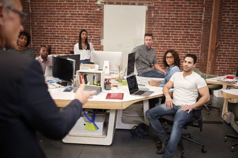 Hög affärsman Talking At Meeting av den tillfälligt klädda affären Team In Open Plan Office fotografering för bildbyråer