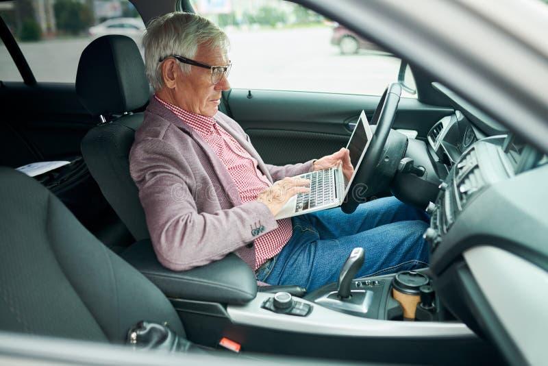 Hög affärsman Using Laptop i bil arkivfoton