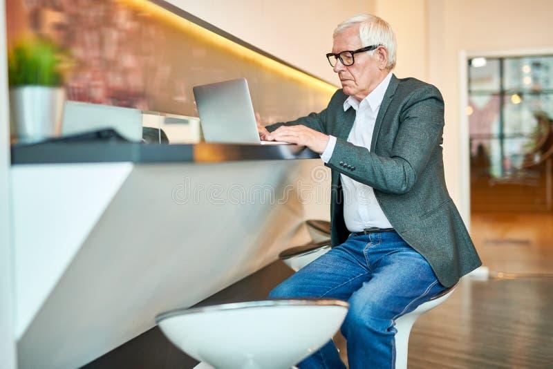 Hög affärsman Using Laptop i stång royaltyfria foton