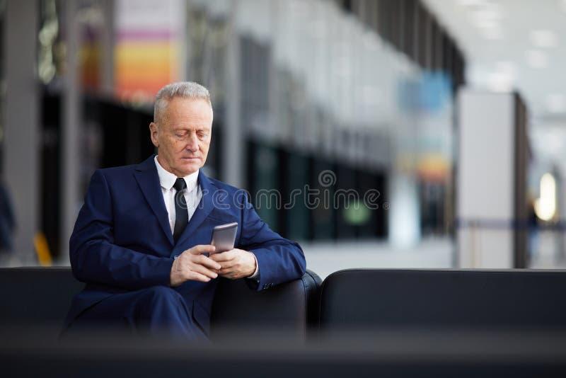 Hög affärsman Using Smartphone i lobby arkivfoton