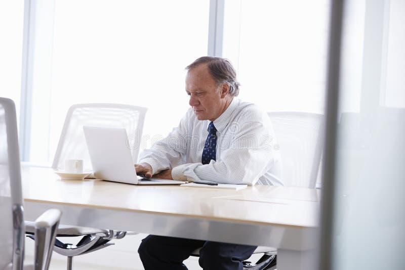 Hög affärsman Working On Laptop på styrelsetabellen royaltyfria bilder