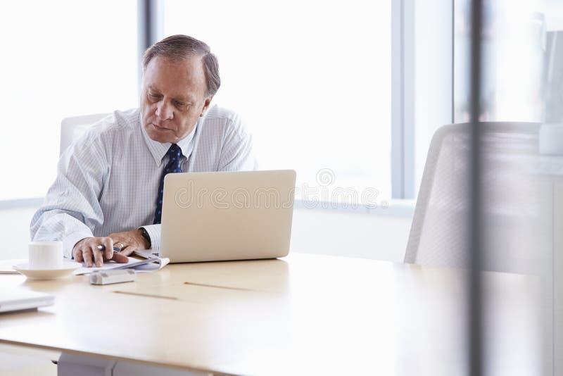 Hög affärsman Working On Laptop på styrelsetabellen royaltyfri foto