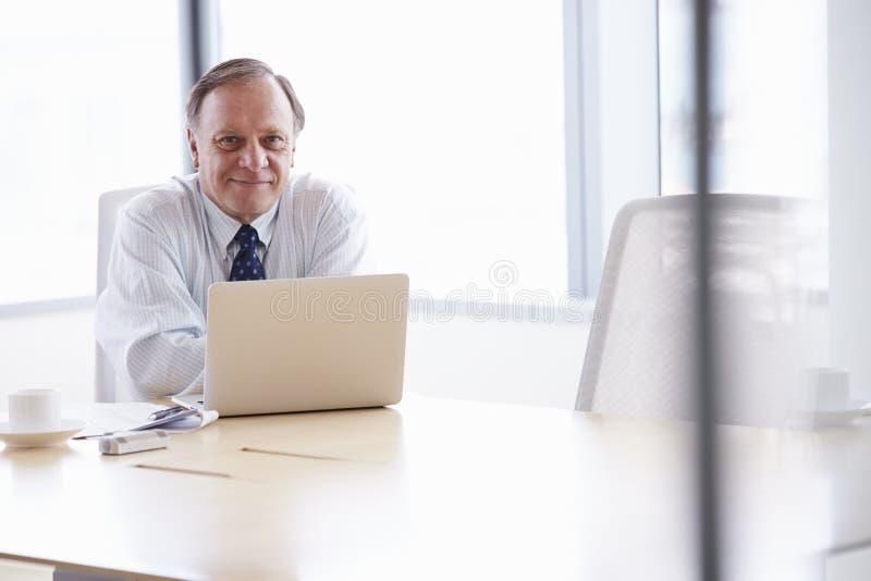 Hög affärsman Working On Laptop på styrelsetabellen arkivfoton
