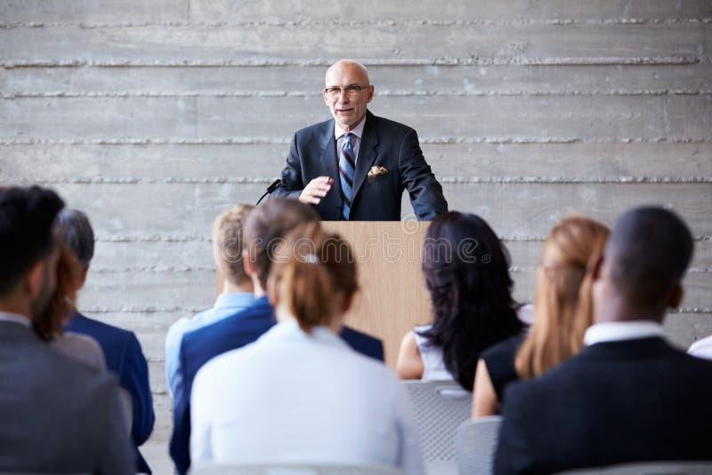 Hög affärsmanAddressing Delegates At konferens royaltyfri foto