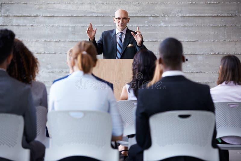 Hög affärsmanAddressing Delegates At konferens royaltyfria bilder