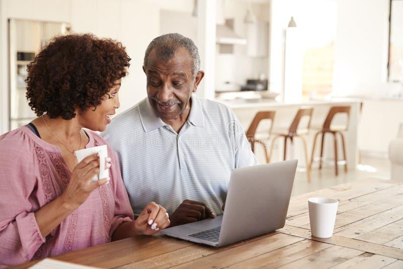 Hög afrikansk amerikanman och hans mellersta åldriga dotter som tillsammans använder en bärbar dator hemma, tätt upp royaltyfri foto