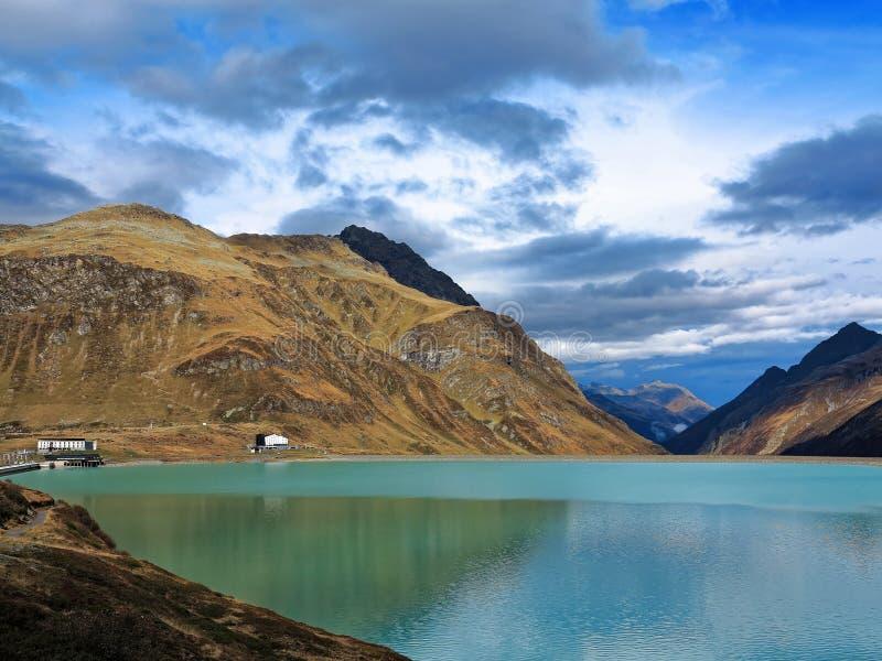 Hög alpin bergsjö med lakesidegästgivargården royaltyfri foto