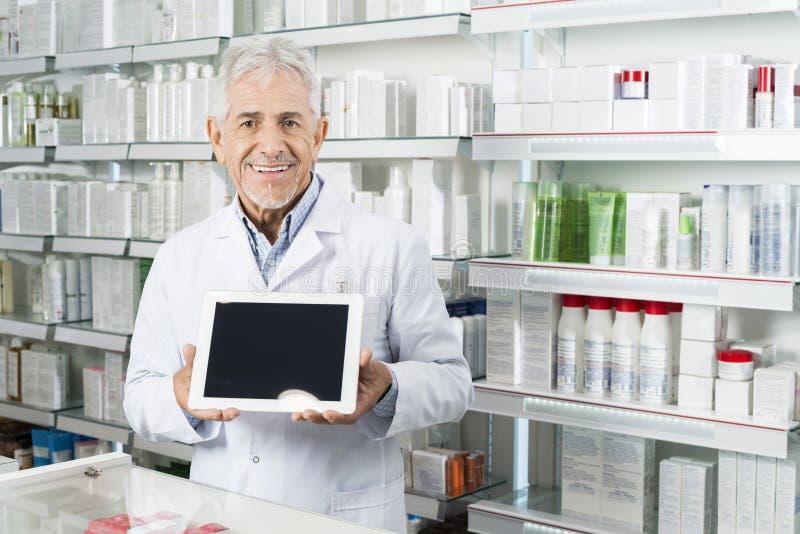 Hög apotekare Holding Digital Tablet med den tomma skärmen arkivfoton