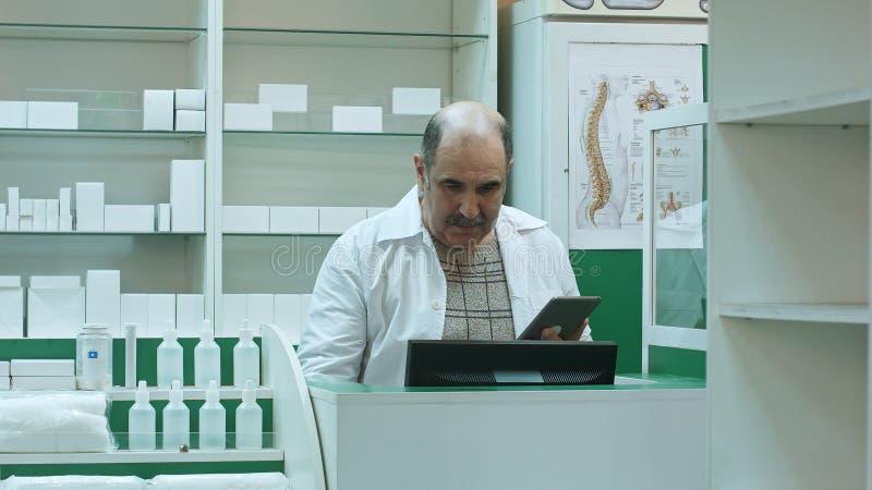 Hög apotekare som använder minnestavlaPC i sjukhusapoteket royaltyfri bild