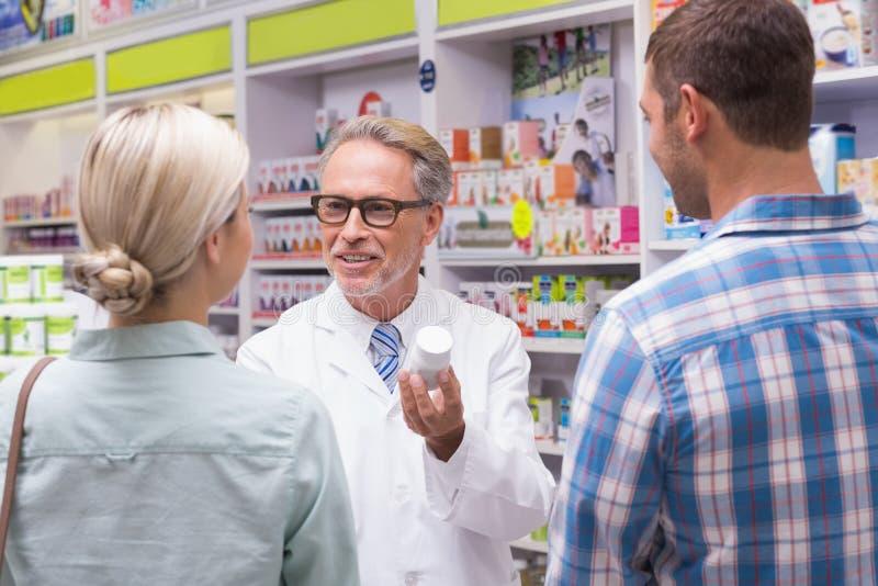 Hög apotekare som förklarar preventivpillerarna till patienten arkivfoton