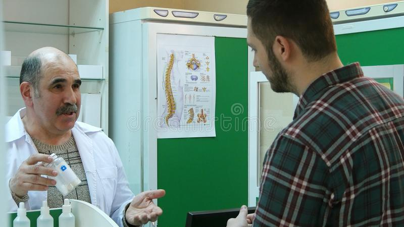 Hög apotekare som talar till den manliga klienten, medan ta medicin av hyllan royaltyfria bilder