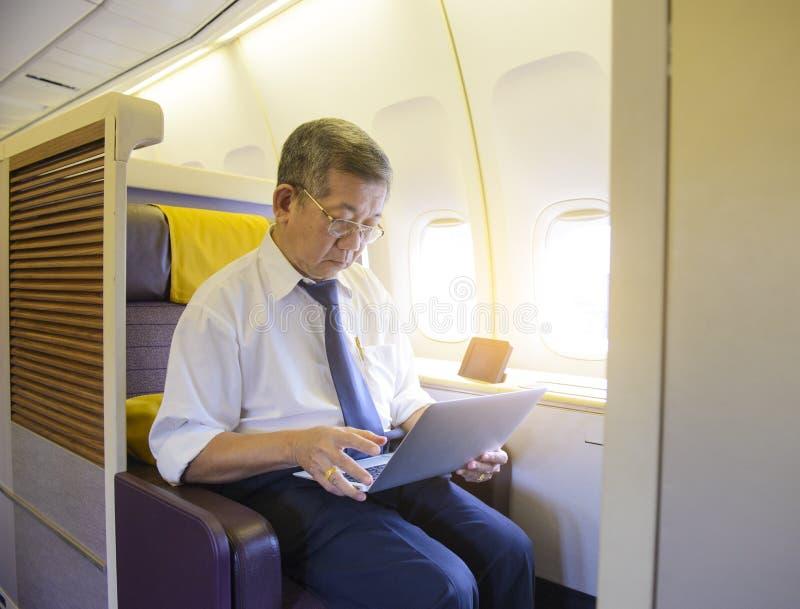 Hög asiatisk man som använder bärbara datorn på första klassflygplanet arkivbild