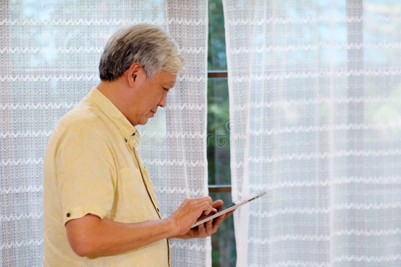 Hög asiatisk man som använder den digitala minnestavlan, medan stå i vardagsrum hemma, folk och teknologi arkivbilder