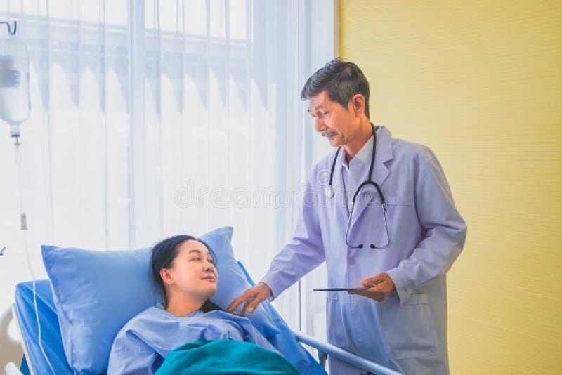 Hög asiatisk manlig doktor som besöker och talar med den medelåldersa kvinnliga patienten på Ward royaltyfria bilder