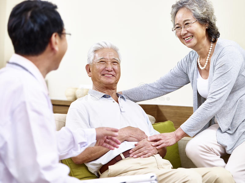 Hög asiatisk patient som tas omsorg av vid familjdoktorn och sp arkivbild