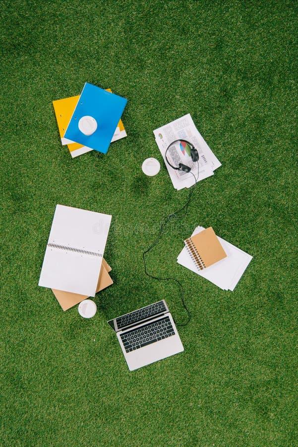 Hög av affärsobjekt och kontorstillförsel som lägger på gräsplan royaltyfria foton