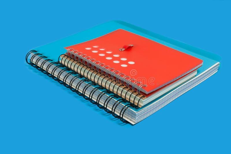 Hög av anteckningsböcker på en blå bakgrund arkivfoto