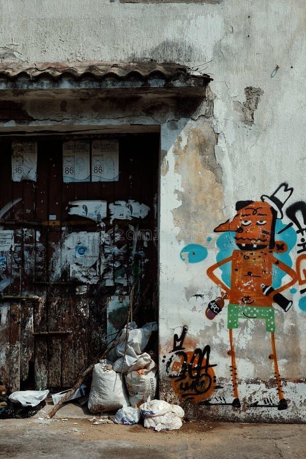 hög av avfall i en dörröppning inom den historiska staden med en grafitti på väggen arkivfoto
