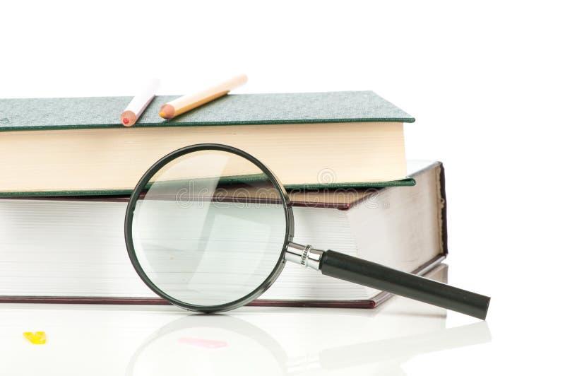 Hög av böcker och förstoringsglaset royaltyfri bild