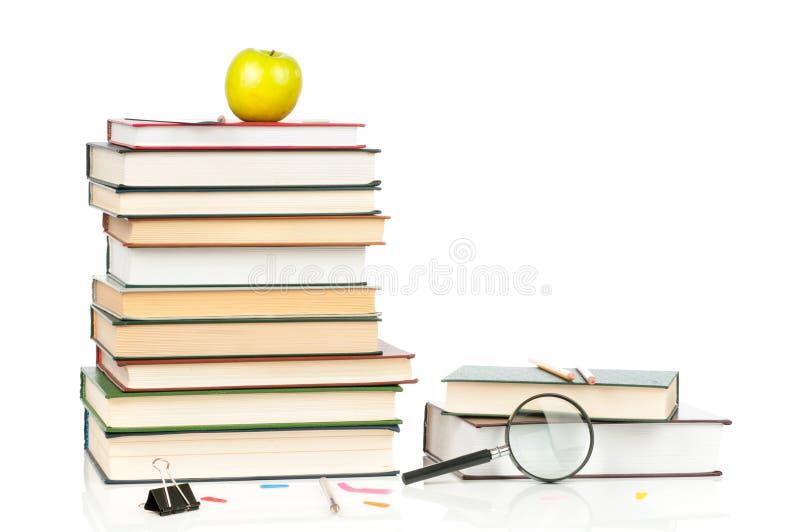 Hög av böcker och förstoringsglaset arkivfoto