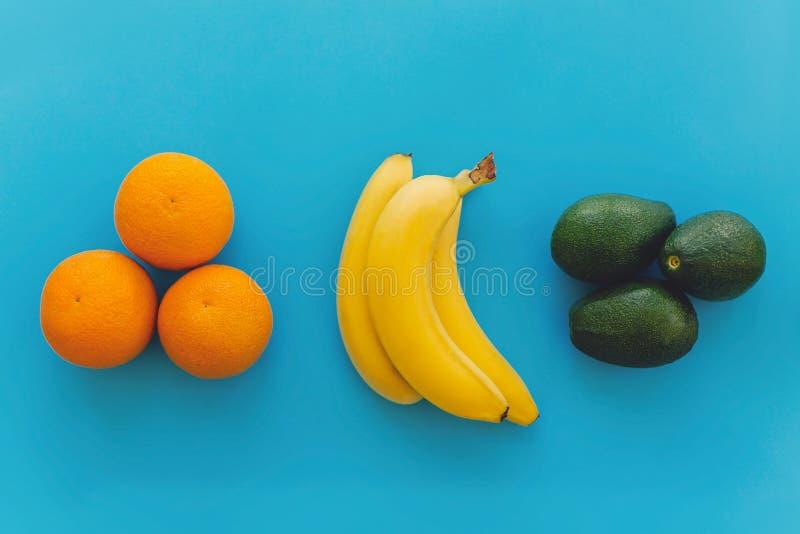 Hög av bananer, apelsiner, avokado på blå moderiktig pappers- backgroun royaltyfria foton