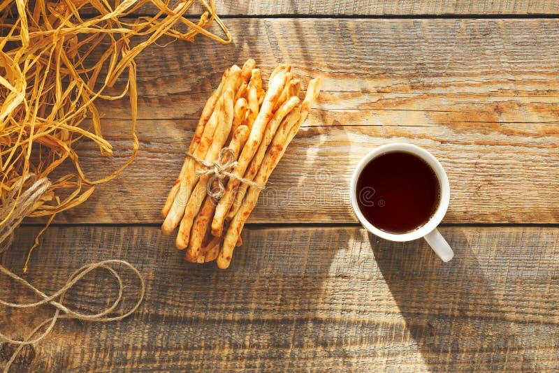 Hög av brödpinnar med te på trätabellen royaltyfria foton