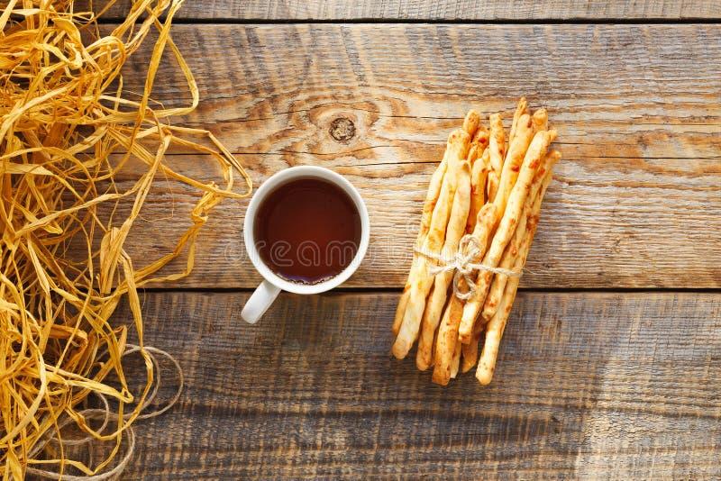 Hög av brödpinnar med te på trätabellen royaltyfri bild