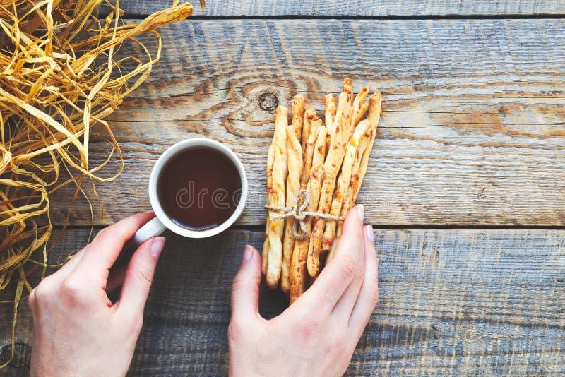 Hög av brödpinnar med te på trätabellen arkivfoto