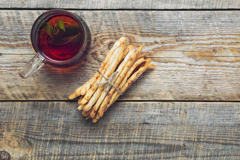 Hög av brödpinnar med te på trätabellen royaltyfri foto