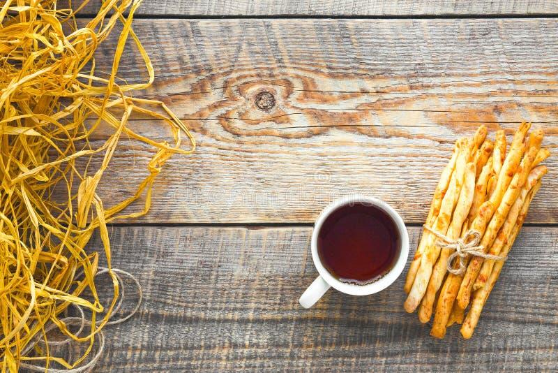 Hög av brödpinnar med te på trätabellen royaltyfria bilder