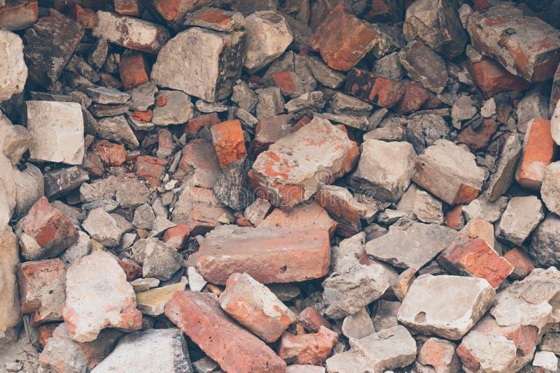 Hög av brutna tegelstenar, bakgrund Textur modell, kollaps för tegelstenvägg Förstörelseyttersida av byggnads fasad skr?p arkivfoto