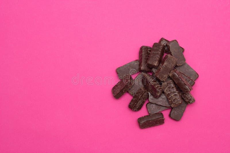 Hög av choklader på rosa bakgrund, kopieringsutrymme, godis arkivbild
